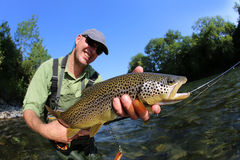 Happy fisherman with brown trout Royalty Free Stock Photo