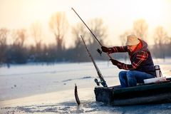 Happy fisherman catch fish on the frozen river in winter. Happy elderly fisherman catch fish on the frozen river in winter Stock Photos
