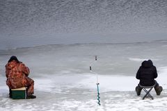 Happy fisherman fighting a fish while ice fishing . stock photo