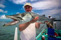 Happy Fisherman holding a Barracuda Royalty Free Stock Image