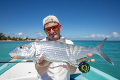 Happy Fisherman holding a Bonefish Royalty Free Stock Images