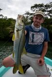Happy Fisherman holding a small Snook Stock Images