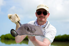 Happy Fisherman holding a Stingray Royalty Free Stock Photos