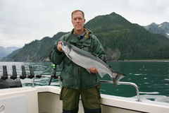 Happy fisherman in holds big silver salmon Royalty Free Stock Image