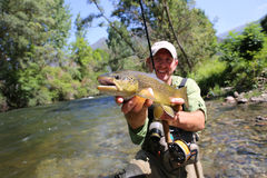 Happy fisherman with a huge brown trout Royalty Free Stock Photos