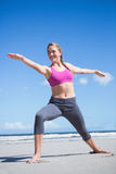 Happy fit blonde standing in warrior position on the beach Royalty Free Stock Photo