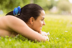 Happy fit brunette lying on the grass Stock Photography