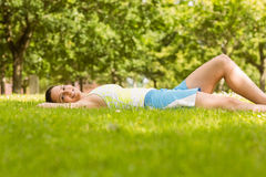 Happy fit brunette lying and relaxing on the grass Royalty Free Stock Photography