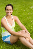 Happy fit brunette sitting on the grass Stock Photos