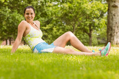 Happy fit brunette sitting and relaxing on the grass Royalty Free Stock Photography