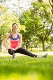 Happy fit brunette stretching on grass Stock Images