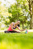 Happy fit brunette stretching on the grass Royalty Free Stock Photo