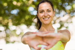 Happy fit brunette stretching in the park Royalty Free Stock Image