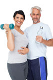 Happy fit couple with dumbbell and water bottle Stock Photos