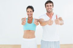 Happy fit couple gesturing thumbs up in fitness studio Royalty Free Stock Photos