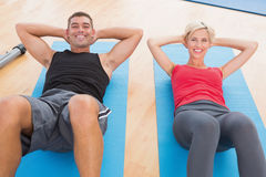 Happy fit couple working on exercise mat Royalty Free Stock Photography