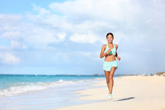 Happy fit female runner running on beach during travel vacation Royalty Free Stock Images