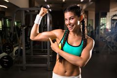 Boasting. Happy fit girl pointing at her muscles and looking at camera with smile Royalty Free Stock Photos