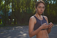 Happy fit girl using phone outdoors Stock Photography
