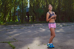 Happy fit girl using phone outdoors Royalty Free Stock Photo