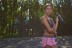 Happy fit girl using phone outdoors Royalty Free Stock Images
