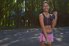 Happy fit girl using phone outdoors Stock Photos