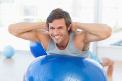 Happy fit man stretching on exercise ball Royalty Free Stock Photo