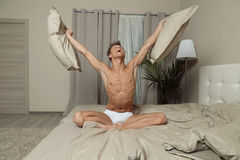 Happy fit man in underwear relax on bed in bedroom. Fit handsome man in underwear relax on bed in bedroom Royalty Free Stock Images