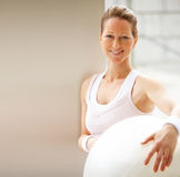 Happy fit mature female holding  a fitness ball Royalty Free Stock Images