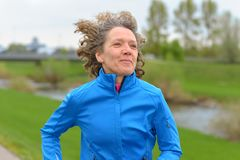 Happy fit middle-aged woman out jogging royalty free stock photography