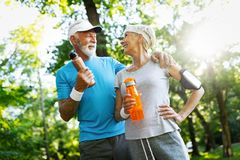 Happy fit senior couple exercising in park stock photography