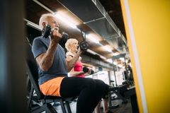 Happy fit mature man in gym working out to stay healthy royalty free stock photos