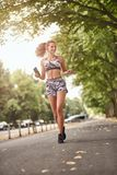 Happy fit slender young woman jogging listening to music. On her smart phone in her hand as she runs along a tree lined urban street in a low angle frontal view stock photos