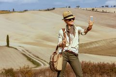 Happy fit solo tourist woman taking selfie with mobile phone stock photos