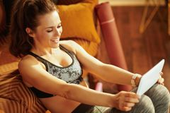 Sports woman using online fitness training program in tablet PC stock photo