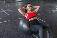 Cheerful adult woman doing abs exercise on ball stock image