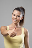 Happy fit sporty woman in yellow tank top showing thumb up gesture at camera Royalty Free Stock Images