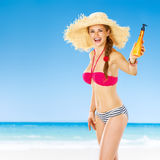 Happy fit woman on beach showing sun cream Stock Image
