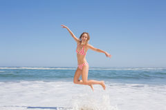 Happy fit woman in bikini jumping on the beach Stock Photo
