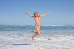 Happy fit woman in bikini jumping on the beach Royalty Free Stock Photos