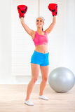 Happy fit woman in boxing gloves rejoicing success Stock Photos