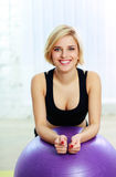 Happy fit woman leaning on the fitball Royalty Free Stock Photos