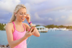 Happy fit woman listening to music during workout outdoors Royalty Free Stock Photography