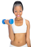 Happy fit woman in sportswear working out with dumbbell Stock Photography