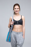 Happy fit woman standing with yoga mat Royalty Free Stock Image