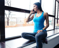 Happy fit woman talking on the phone Royalty Free Stock Image