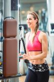 Happy fit woman wearing pink fitness bra while exercising at the gym. Happy and beautiful fit woman wearing pink fitness bra while exercising cable rope triceps Stock Photos
