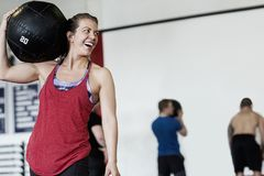 Woman Carrying Medicine Ball On Shoulder Royalty Free Stock Image