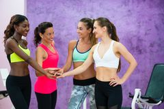 Happy fit women putting hands together before group workout clas stock image