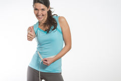 Happy fit young woman measuring her waistline. Caucasian happy fit young woman measuring her waistline after diet, on gray background stock photo